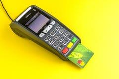 Moscú, Rusia, 13 11 2018 Terminal del pago con tarjeta de crédito en fondo amarillo Tarjeta plástica verde Mastercard insertada e fotografía de archivo