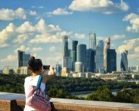 Moscú, Rusia, verano 2016 - la muchacha toma las fotos de las señales, edificios de la ciudad de Moscú Foto de archivo libre de regalías