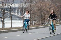 mosc? Rusia 9 de abril de 2019 Dos chicas jóvenes montan alrededor de la ciudad en las bicicletas azules Forma de vida sana se di imagen de archivo