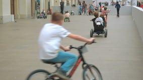 Mosc?, Rusia - 12 de abril de 2019: Ni?os que montan las bicicletas, las vespas y los peque?os coches en el pasillo del centro de metrajes