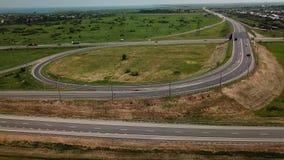 mosca aérea 4K sobre la intersección moderna del camino de la carretera en paisaje rural metrajes