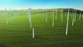 A mosca aérea sobre cresce as turbinas eólicas acima de construção que geram a energia ilustração stock
