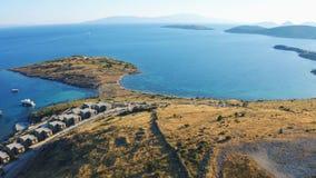 Mosca aérea sobre a ilha com as casas do recurso pelo mar Montanhas no fundo Boa vinda ao conceito de Turquia vídeos de arquivo