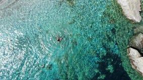 Mosca aérea sobre la mujer feliz splasing y que da vuelta en el mar claro almacen de metraje de vídeo