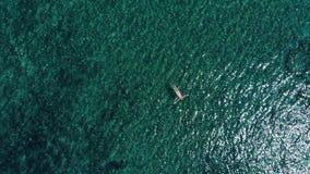 Mosca aérea sobre la mujer que nada solamente en el océano metrajes