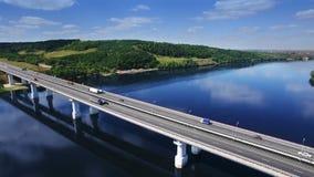 Mosca AÉREA sobre a maneira de estrada da estrada da estrada da ponte do tráfego e rio azul com árvores floresta, Europa, Rússia, video estoque
