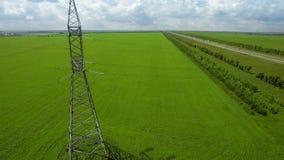 Mosca ascendente de alto voltaje aérea de la elevación de la hierba verde del fondo del cielo de la luz del verano de la torre almacen de metraje de vídeo