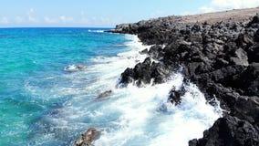 Mosca baja aérea sobre las rocas volcánicas y el mar azul azul, Creta de la playa almacen de metraje de vídeo
