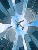Mosca branca do avião acima da cidade moderna Fotos de Stock
