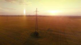 Mosca caliente de la cámara de la luz de la tarde del verano de alto voltaje AÉREO de la torre cerca del cable de la electricidad almacen de metraje de vídeo