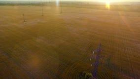 Mosca caliente de la cámara de la luz de la tarde del verano de alto voltaje AÉREO de la torre sobre línea del cable de la electr metrajes