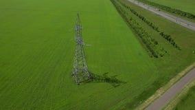 Mosca de alta tensão aérea do panorama do círculo da órbita da grama verde do fundo do céu azul do verão da torre filme
