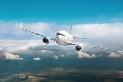 Mosca del aeroplano del pasajero en nubes cubiertas y cielo azul fotografía de archivo libre de regalías