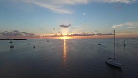 Mosca del fuco indietro dal tramonto sopra l'oceano video d archivio