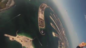 Mosca del paracadutista sopra il Dubai paracadute Giorno pieno di sole Volo estremo Oceano Litorale archivi video