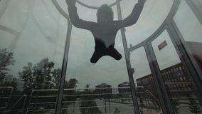 Mosca del skydiver del hombre en el túnel de viento hacia arriba y hacia abajo El volar en un túnel que salta en caída libre almacen de metraje de vídeo