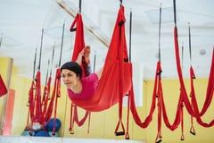 Mosca di pratica di yoga della giovane bella donna con un'amaca nello studio luminoso Volo, forma fisica, allungamento, equilibri Fotografie Stock