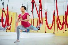 Mosca di pratica di yoga della giovane bella donna con un'amaca nello studio luminoso Volo, forma fisica, allungamento, equilibri Immagine Stock Libera da Diritti
