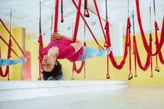 Mosca di pratica di yoga della giovane bella donna con un'amaca nello studio luminoso Volo, forma fisica, allungamento, equilibri Fotografia Stock Libera da Diritti