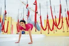 Mosca di pratica di yoga della giovane bella donna con un'amaca nello studio luminoso Volo, forma fisica, allungamento, equilibri Fotografia Stock