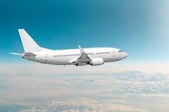 Mosca do avião do passageiro em nuvens nublado acima de uma altura e no céu azul Foto de Stock