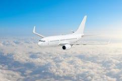 Mosca do avião do passageiro em uma altura acima das nuvens e do céu azul Imagens de Stock Royalty Free