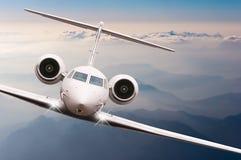 Mosca do avião sobre nuvens e montanha dos cumes no por do sol Vista dianteira de um avião grande do passageiro ou da carga, jato fotos de stock