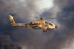 Mosca do helicóptero de ataque de AH-64 Apache acima da base da força aérea de Hatzerim perto de Beersheba, Israel na frente do f fotografia de stock royalty free
