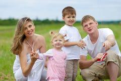 Mosca felice della famiglia un cervo volante insieme nel campo di estate Fotografia Stock