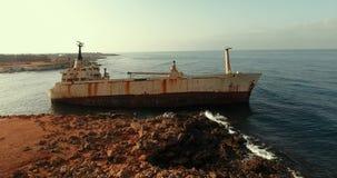 Mosca lejos de la nave inundada Las ondas se rompen en las piedras almacen de metraje de vídeo