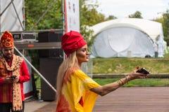 Mosca, parco su Krasnaya Presnya, il 5 agosto 2018: una giovane donna graziosa in un copricapo rosso tiene il suo telefono in sua fotografie stock libere da diritti