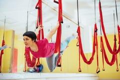 Mosca practicante de la yoga de la mujer hermosa joven con una hamaca en el estudio brillante El concepto de salud mental y físic Imagenes de archivo
