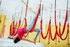 Mosca practicante de la yoga de la mujer hermosa joven con una hamaca en el estudio brillante El concepto de salud mental y físic Fotografía de archivo