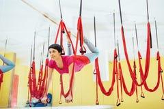 Mosca practicante de la yoga de la mujer hermosa joven con una hamaca en el estudio brillante El concepto de salud mental y físic Fotografía de archivo libre de regalías