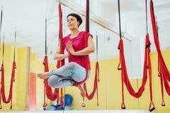 Mosca practicante de la yoga de la mujer hermosa joven con una hamaca en el estudio brillante El concepto de salud mental y físic Imagen de archivo