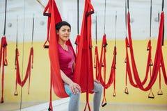 Mosca practicante de la yoga de la mujer hermosa joven con una hamaca en el estudio brillante El concepto de salud mental y físic Imágenes de archivo libres de regalías