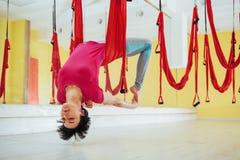 Mosca practicante de la yoga de la mujer hermosa joven con una hamaca en el estudio brillante El concepto de salud mental y físic Fotos de archivo