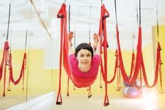 Mosca practicante de la yoga de la mujer hermosa joven con una hamaca en estudio Foto de archivo