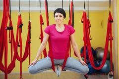 Mosca practicante de la yoga de la mujer hermosa joven con una hamaca en estudio Fotografía de archivo libre de regalías