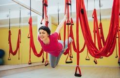 Mosca practicante de la yoga de la mujer hermosa joven con una hamaca en estudio Imagen de archivo