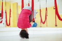 Mosca practicante de la yoga de la mujer hermosa joven con una hamaca en estudio Imagen de archivo libre de regalías