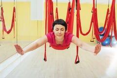 Mosca practicante de la yoga de la mujer hermosa joven con una hamaca en estudio Foto de archivo libre de regalías