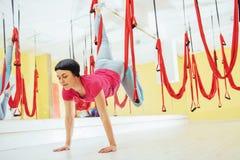 Mosca practicante de la yoga de la mujer hermosa joven con una hamaca en estudio Fotos de archivo libres de regalías