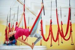 Mosca practicante de la yoga de la mujer hermosa joven con una hamaca en estudio Fotografía de archivo