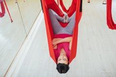 Mosca practicante de la yoga de la mujer hermosa joven con una hamaca en estudio Fotos de archivo