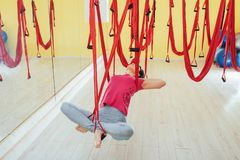 Mosca practicante de la yoga de la mujer hermosa joven con una hamaca en estudio Imagenes de archivo