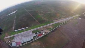 Mosca profesional del skydiver en el paracaídas en cielo en puesta del sol horizonte adrenalina metrajes