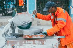 Mosca, Russia - 14 agosto 2015: un costruttore taglia un pezzo di pietra del granito su una macchina circolare della sega Ricostr immagine stock