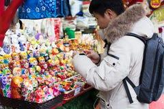 Mosca, Russia - 21 dicembre 2017: Il giovane uomo del compratore seleziona Toy Ru Fotografie Stock Libere da Diritti