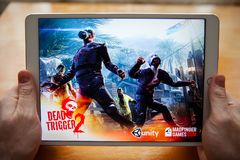 Mosca/Russia - 25 febbraio 2019: Ipad bianco a disposizione Sullo schermo, caricante l'innesco 2 dei morti del gioco fotografia stock libera da diritti